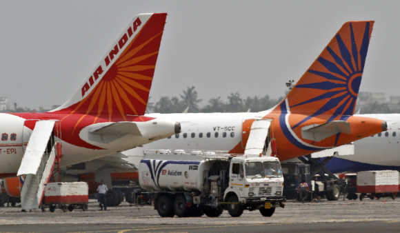 Fuel tanker moves past Air India passenger jets parked at an airport in Kolkata.