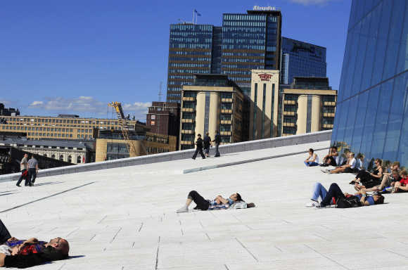 People sunbathe in front of the Oslo Opera House, the home of the Norwegian National Opera and Ballet, in Oslo.