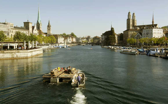 A worker steers a boat and a pontoon on the Limmat River during sunny spring weather in Zurich.
