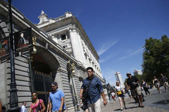 Tourists walk past the Royal Palace in Madrid, Spain.