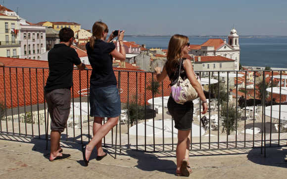 Tourists watch the Lisbon old downtown in front of the Tagus riverside, Portugal.