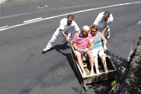 Carreiros (sledge drivers) push tourists in Monte on the Atlantic island of Madeira, Portugal.