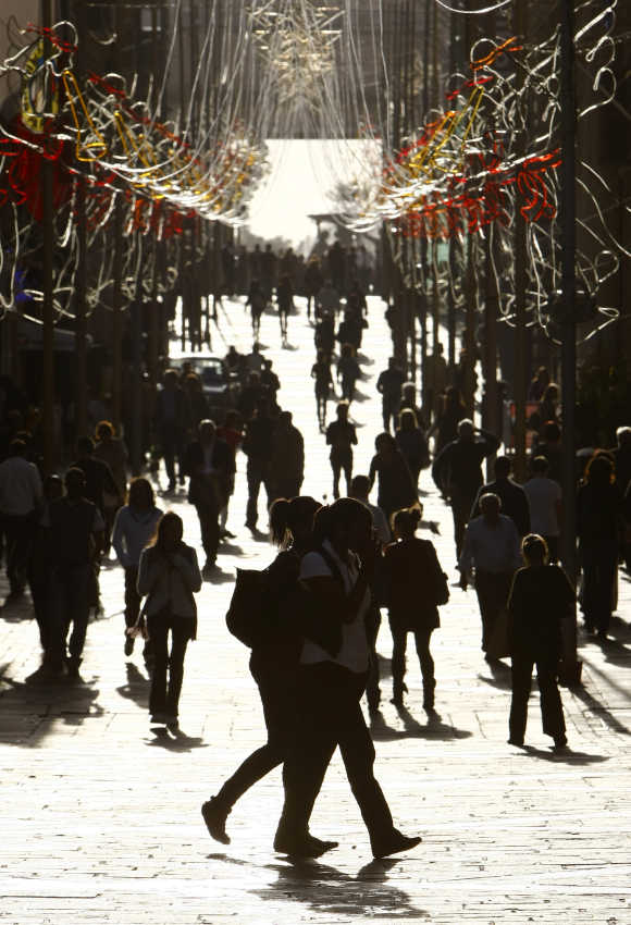 Pedestrians and shoppers walk on a street decorated with Christmas lights in Valletta, Malta.