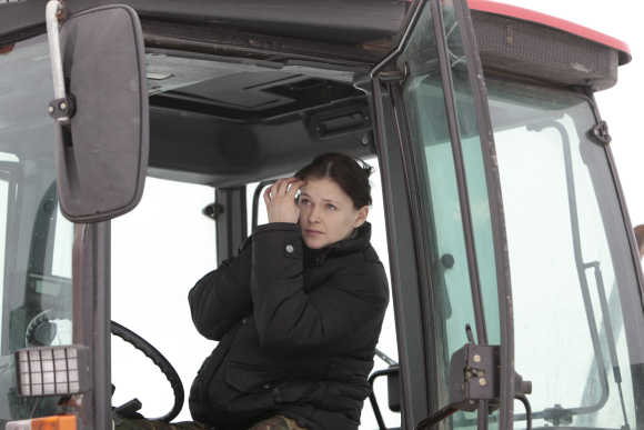 Ekaterina Shestakovskaya looks in the mirror as she drives a tractor in Kamenuki, 360km south-west of Minsk, Ukraine.