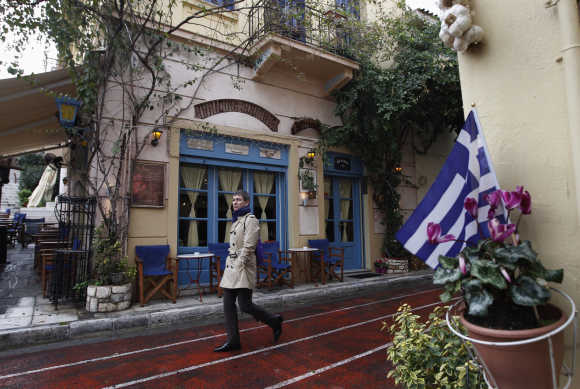 A man walks in front of a cafe at Plaka tourist district in Athens.