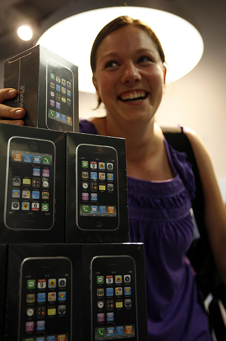 One of the first iPhone buyers in Switzerland poses for photographers next to Apple's new iPhone 3G as it went on sale in Zurich.