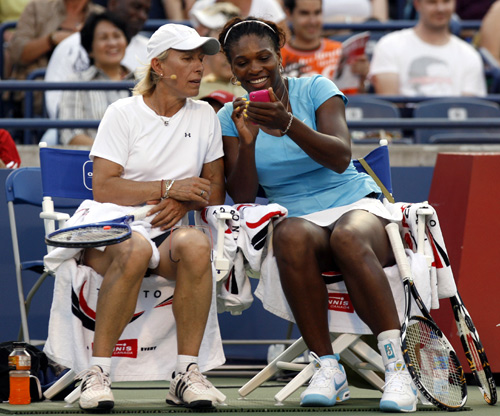 Martina Navratilova (L) looks at Serena Williams' Iphone while playing in an exhibition doubles match at the Rogers Cup tennis tournament in Toronto.