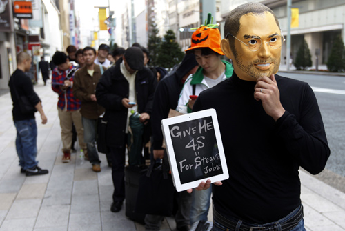 A man wearing a mask of Apple founder Steve Jobs stands in a line to buy an iPhone 4S in front of an Apple Store in Tokyo.