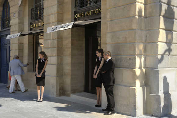 Hostesses stand in front of LVMH's Louis Vuitton's jewellery store on Place Vendome in Paris.