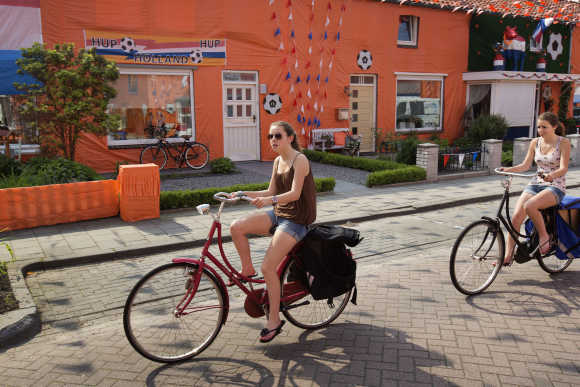 Two girls ride their bicycles in the Irenestraat in Goirle, the Netherlands.