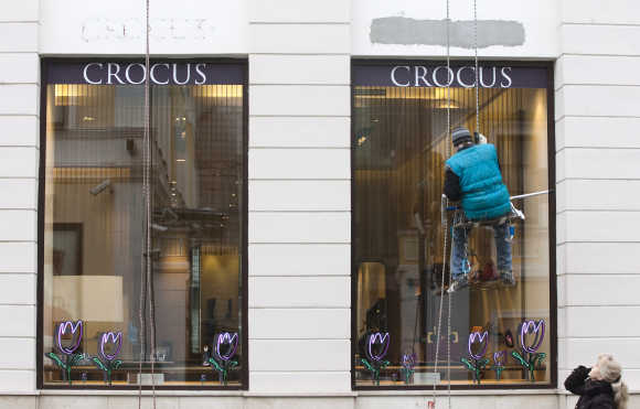 A window cleaner abseils in front of a boutique of the Crocus luxury retailer in Moscow.