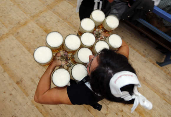 A waitress carries beer after the opening of Oktoberfest in Munich, Germany.