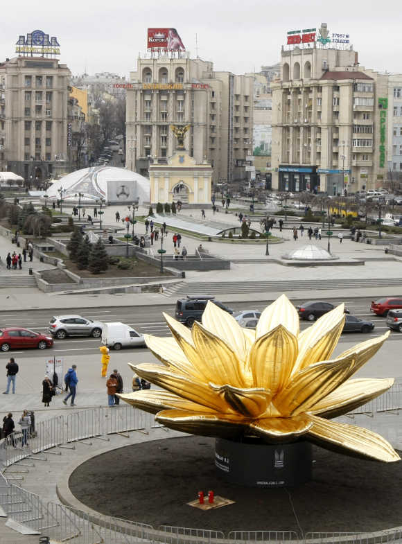 Pedestrians pass an inflatable lotus at Independence Square in Kiev.