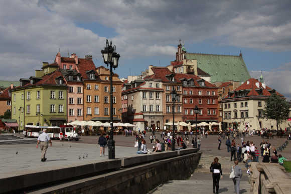 People walk at Plac Zamkowy in Warsaw's Old Town.