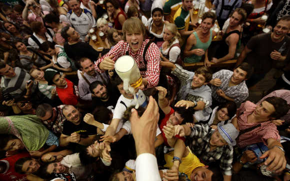 Revellers scuffle for the first free beer in the traditional one-litre beer mug at the opening of the World's biggest beer fest, the Munich Oktoberfest, at the Theresienwiese in Munich.