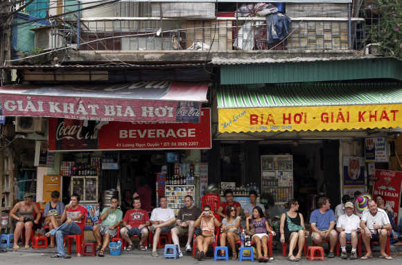 Tourists sit on stools and drink beer at the old quarters in Hanoi.