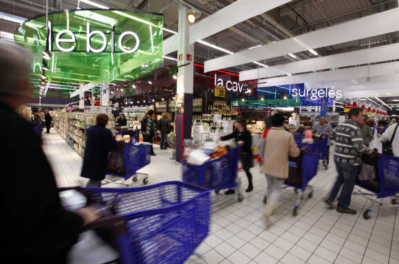 Customers push shopping trolleys inside the Carrefour Planet supermarket in Nice, France.