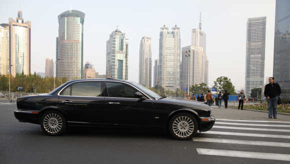 A Jaguar car stops at a pedestrian crossing in the Pu Dong financial district of Shanghai.