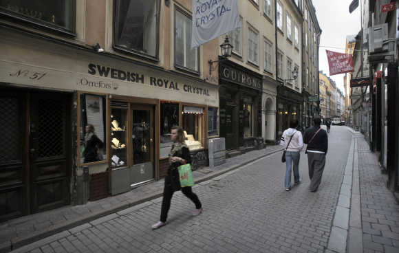 Pedestrians walk down the main shopping street in Stockholm's Gamla Stan or Old Town district.