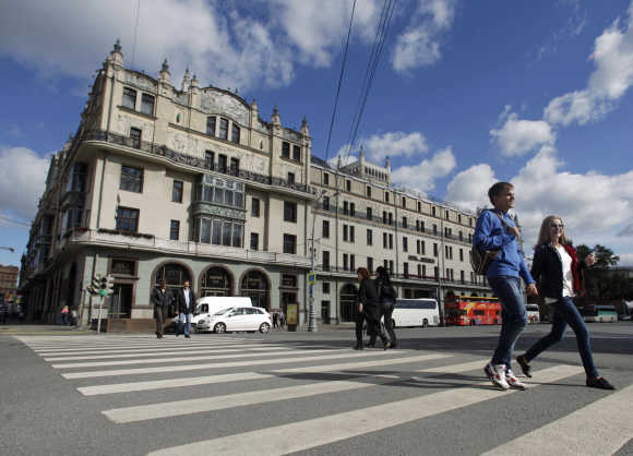 People cross the road near Metropol hotel in Moscow.