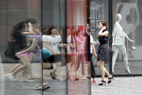 Pedestrians walk past a foreign-owned clothing store in Beijing's Sanlitun Area.