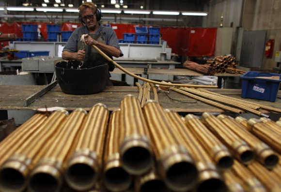 An employee checks a copper hose in Sao Paulo, Brazil.