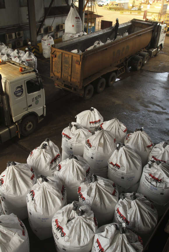 Workers load sacks of nickel ore into trucks in Indonesia's south Sulawesi province.