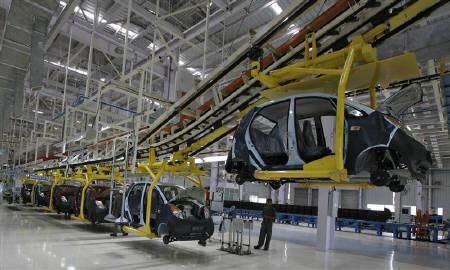An employee stands inside the Tata Nano plant at Sanand in Gujarat