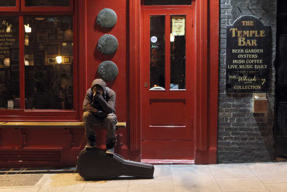 A musician sits on a bench outside a pub in Temple Bar, Dublin.