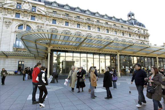Toursits walk past the Orsay Museum in Paris.