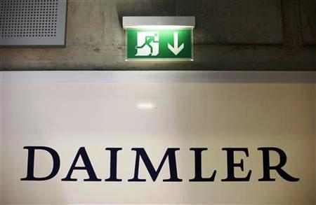 An emergency exit sign is pictured above a logo of German car manufacturer Daimler AG, before the annual news conference in Stuttgart.