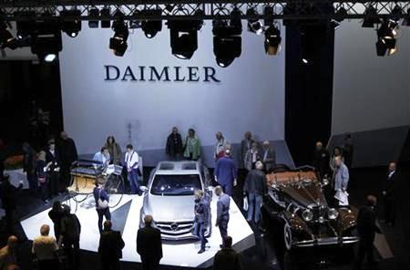 People look at historic and future Daimler cars at a Daimler annual shareholder meeting in Berlin.