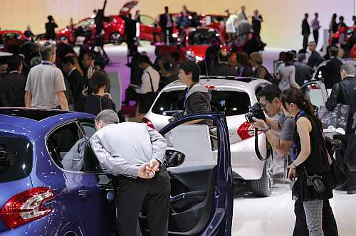 Visitors look at cars on media day at the Paris Motor Show 2012