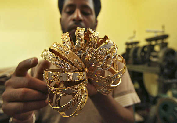 A worker counts gold bangles at a jewellery-making workshop in Jammu.