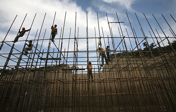 Workers fasten iron rods at the construction site of a bridge in Jammu.