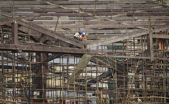 Labourers work at the construction site of a Metro station in Mumbai.