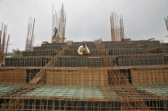 Labourers work at a construction site of a stadium in Agartala, Tripura.