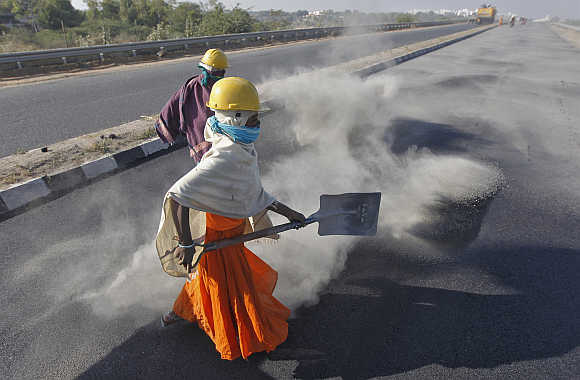 A woman labourer spreads black ash over a road at Raipur village in Gujarat.