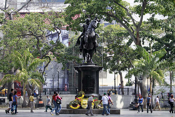 Poeple walk next to the statue of national hero Simon Bolivar in Caracas, Venezuela.