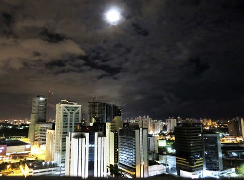 The moon rises above buildings in Salvador, Brazil.