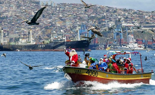 Ruben Torres, dressed in a Santa Claus outfit, and fishermen wave to people from a boat on Christmas Eve along the coast of Valparaiso city, about 121 km (75 miles) northwest of Santiago.