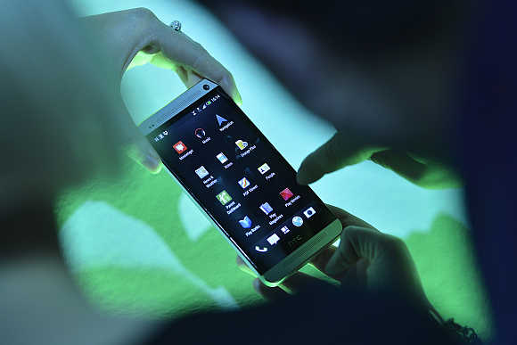 Guest uses a sample phone at the launch of the HTC One smartphone in London.