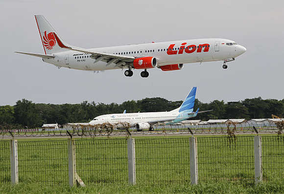 A Lion aeroplane prepares to land as a Garuda plane queues to take-off at the Sukarno-Hatta airport in Tangerang on the outskirts of Jakarta, Indonesia.