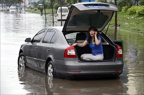 A woman talks on her mobile phone at the trunk of her car as she waits for rescue on a flooded street in Taiyuan, Shanxi province.