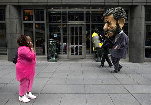 A woman looks as two men dressed as Iranian leader Mahmoud Ahmadinejad walk toward a protest on the sidelines of the United Nations General Assembly in New York.