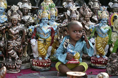 Prem, the son of an idol vendor, plays with a mobile phone in front of the idols of Hindu god Krishna at a roadside on the eve of the Hindu festival of Janmashtami.