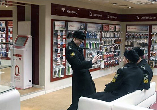 A Russian cadet uses a mobile phone to photograph other cadets in an MTS shop in St.Petersburg.