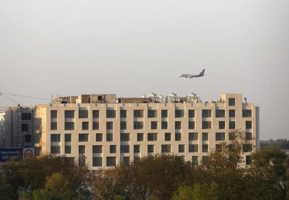 A SpiceJet Airlines aircraft flies past newly-constructed hotels on the way to landing at the Indira Gandhi International Airport in New Delhi.