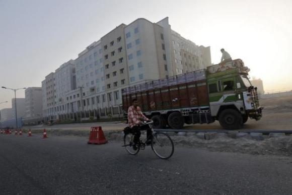 A man rides his bicycle past newly-constructed hotels outside the Indira Gandhi International Airport in New Delhi.