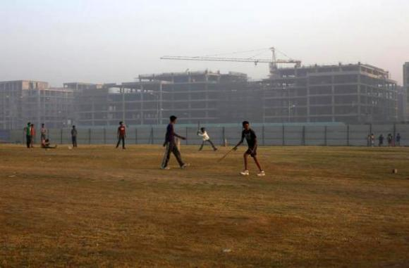 Youths play cricket in front of hotels being constructed outside the Indira Gandhi International Airport in New Delhi.